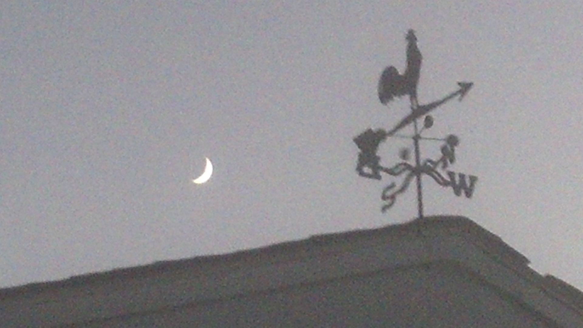 Moon rising over the roofline